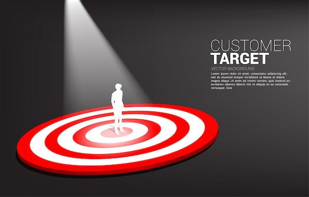 Schattenbild des geschäftsmannes, der auf mitte der dartscheibe mit scheinwerferlicht steht. geschäftskonzept von marketingziel und kunde. unternehmensvision mission und ziel.