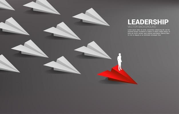 Schattenbild des geschäftsmannes, der auf rotem origami-papierflugzeug führend gruppe von weiß steht. geschäftskonzept der führung und vision mission.
