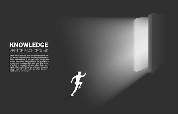 Schattenbild des geschäftsmannes, der im licht vom offenen buch läuft. konzept der kenntnis des buches