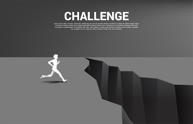 Schattenbild des geschäftsmannes, der läuft, um über die lücke zu springen. konzept der geschäftlichen herausforderung und des mutes