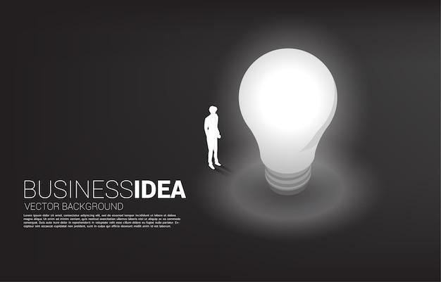 Schattenbild des geschäftsmannes, der mit glühbirne steht. geschäftskonzept der kreativen idee und lösung.