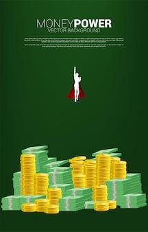 Schattenbild des geschäftsmannes, der vom münzen- und banknotenstapel fliegt. konzept der steigerung und des wachstums im geschäft.