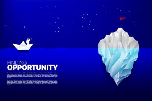 Schattenbild des geschäftsmannes mit teleskop auf dem papierschiff, das zur flagge auf eisberg schaut.