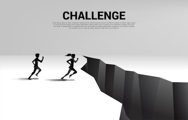 Schattenbild des geschäftsmannes und der geschäftsfrau, die laufen, um über die lücke zu springen. konzept der geschäftlichen herausforderung und des wettbewerbs.