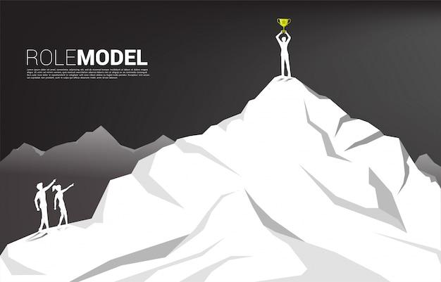 Schattenbild des geschäftsmannes und der geschäftsfrau zeigen vorwärts auf geschäftsmann mit trophäe auf berg. konzept von berufseinstieg und vorbild.