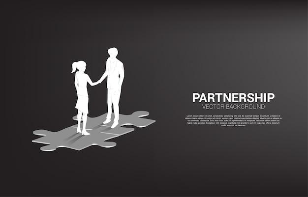 Schattenbild des geschäftsmannhändedrucks auf stichsäge. konzept der teamarbeit partnerschaft und zusammenarbeit.