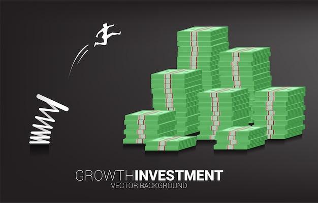 Schattenbild des geschäftsmannsprungs zum geldbanknotenstapel mit frühling. konzept von boost und wachstum im geschäft.