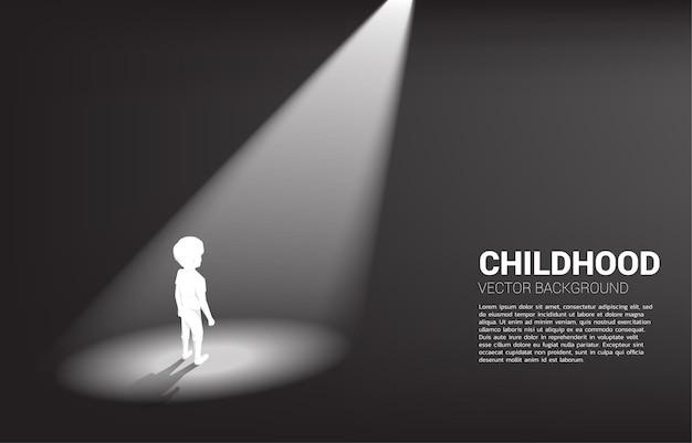 Schattenbild des jungen, der im scheinwerferlicht steht