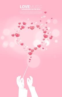 Schattenbild des leiters hand halten stab mit herzballon fliegen. konzepthintergrund für liebeslied und konzertthema.