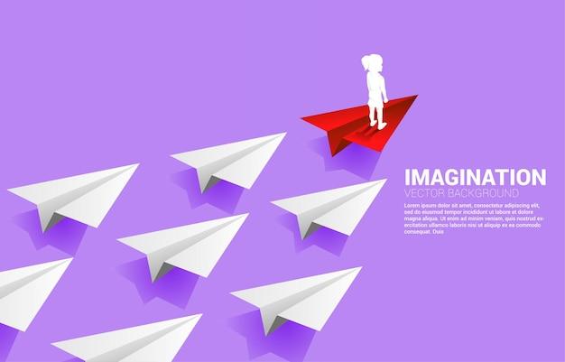 Schattenbild des mädchens, das auf rotem origami-papierflugzeug führend gruppe von weiß steht. konzept der kinderphantasie und bildung.
