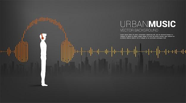 Schattenbild des mannes mit kopfhörer und schallwellenmusik-ausgleichshintergrund mit stadthintergrund. audiovisuelles kopfhörersymbol mit linienwellengrafikstil