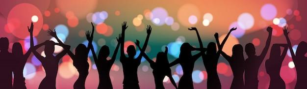 Schattenbild-leute, die über feiertags-feuerwerks-hintergrund-partei-feier-konzept tanzen