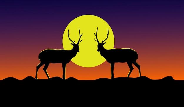 Schattenbild von zwei rotwild, die auf einem berg mit einem gelben mond im hintergrund stehen.