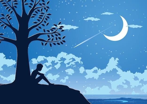 Schattenbildentwurf des einsamen jungen mannes in der stillen nacht unter einem baum
