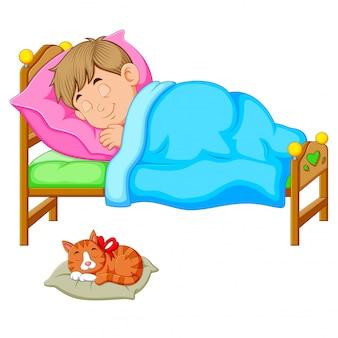 Schlafender junge im bett mit einem kätzchen