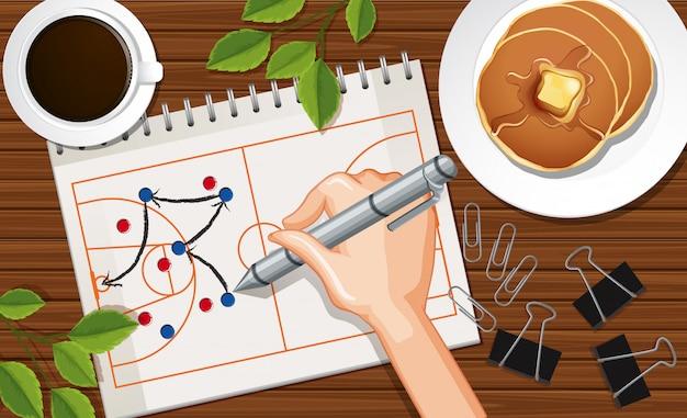 Schließen sie die hand, die basketballflugzeug auf papier mit kaffeetasse und pfannkuchen auf schreibtischhintergrund schreibt