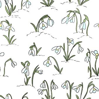 Schneeglöckchenblumen auf dem nahtlosen muster des schnees