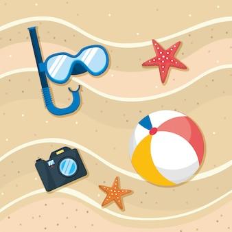 Schnorchelmasken mit seesternen und kamera mit ball im strandsand