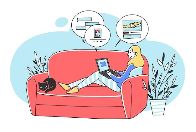 Schöne frau, die am sofa mit laptop sitzt