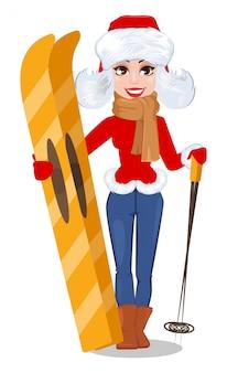 Schöne frau in der winterkleidung, die skis hält.