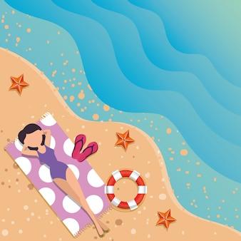 Schöne frau mit badeanzug im handtuch am strand entspannen