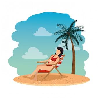 Schöne frau mit badeanzug im liegestuhl am strand sitzen