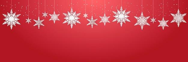 Schöne hängende schneeflocken und fallender schnee auf rotem hintergrundanzug für weihnachts-, neujahrs- und winterfahne, grußkarte