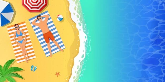 Schöne junge frau und mann, die am strand ein sonnenbad nehmen. draufsicht auf die liegenden leute.