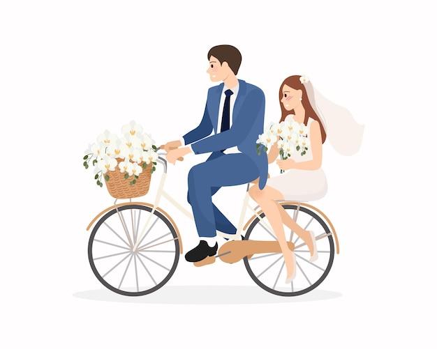 Schöne junge gerade verheiratete hochzeitspaar fahren fahrrad isoliert
