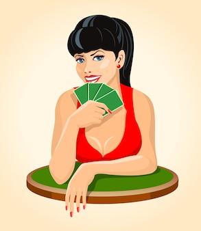 Schöne lächelnde brunettefrau im roten kleid mit spielkarten, die am tisch sitzen. poker, brückensymbol.