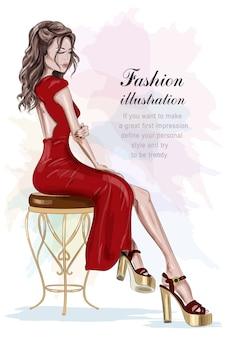 Schöne modefrau im roten kleid, das auf weinlesestuhl sitzt.