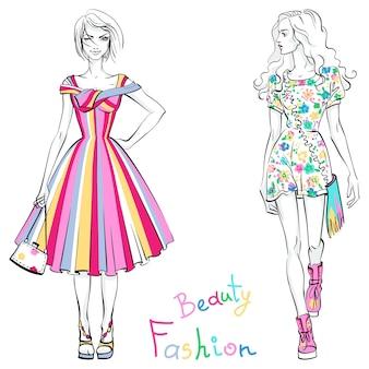 Schöne modische mädchen in bunten kleidern mit aufschrift beauty and fashion