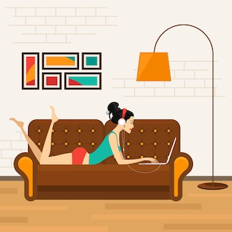 Schönes mädchen, das auf sofa mit laptop liegt und musik auf kopfhörern hört.