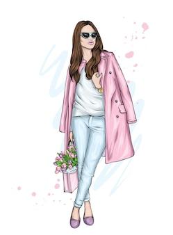 Schönes mädchen in einem stilvollen mantel und tulpen