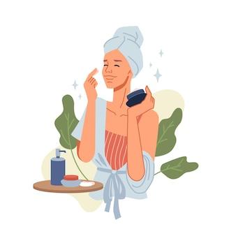Schönheitsmädchen kümmern sich um die haut beim auftragen von kosmetika