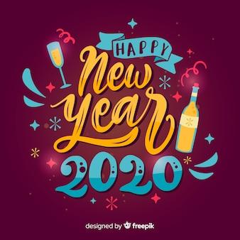 Schriftzug frohes neues jahr 2020 und champagner