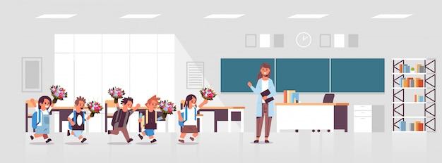 Schüler, die blumen an die lehrerin geben, die vor der tafel in der klassenzimmerausbildung steht, zurück zum modernen klassenzimmerinnenraum des schulkonzepts