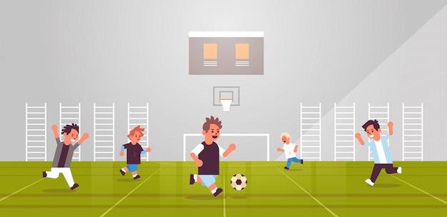 Schüler spielen fußball grundschulkinder, die spaß mit fußball in sportkomplexaktivitäten aktivitätenkonzept schulgymnastik interieur flach in voller länge horizontal haben