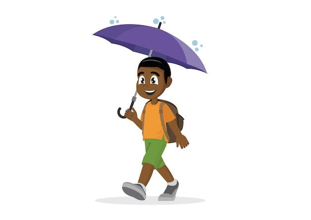 Schulafrikanischer junge mit regenschirm im regen.