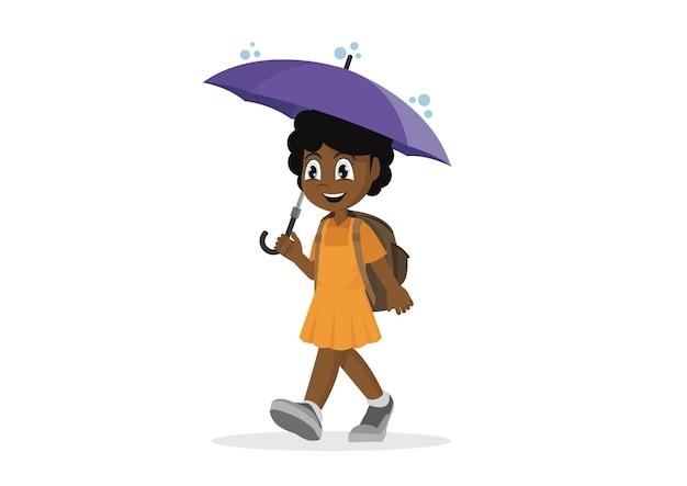 Schulafrikanisches mädchen mit regenschirm im regen.