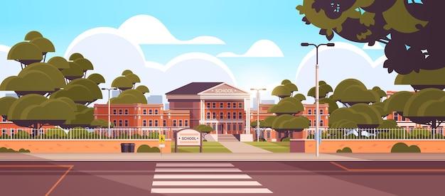 Schulgebäude leerer vorgarten mit grünen bäumen straße zebrastreifen sommer stadtbild hintergrund