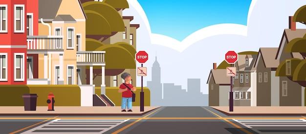 Schuljunge mit rucksack, der in der nähe des roten stoppschildes auf der straßenverkehrssicherheit der stadt steht