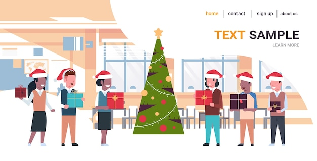 Schulkinder, die geschenkboxenschüler in den weihnachtsmützen halten, die nahe tannenbaumweihnachtsfeiertagsfeierkonzept des modernen klassenzimmerinnenraums stehen