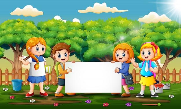 Schulkinder, die leeres schild im park halten