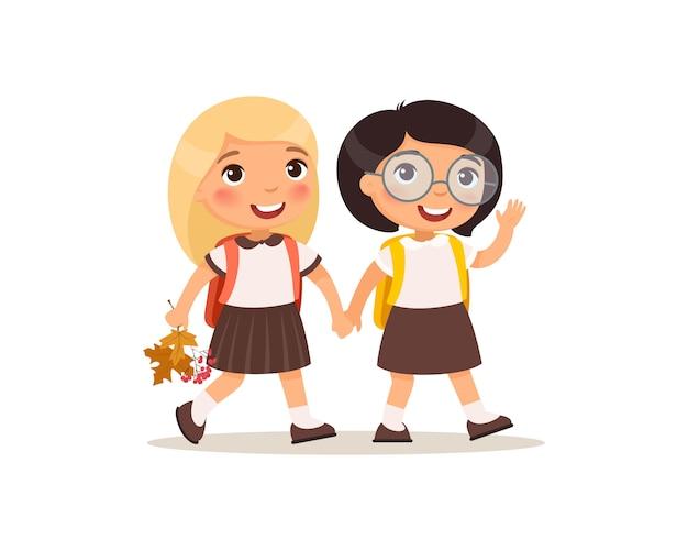 Schulmädchen gehen zur schule flache vektorillustration. paar schüler in uniform händchenhalten isolierte zeichentrickfiguren. zwei glückliche grundschüler mit rucksäcken, die hand und gruß winken