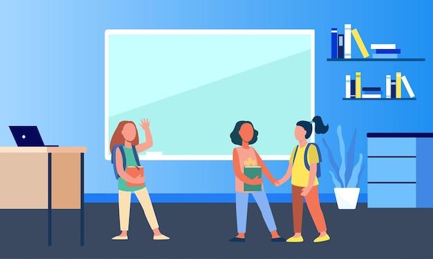 Schulmädchen treffen sich im klassenzimmer. gruppe von freunden, klassenkameraden, die hände halten und hallo flache vektorillustration winken. kommunikation, freundschaftskonzept