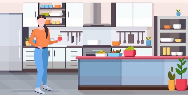 Schwangere frau, die apfelmädchen hält frisches obst und gemüse schwangerschaft mutterschaft konzept moderne küche interieur in voller länge horizontal essen