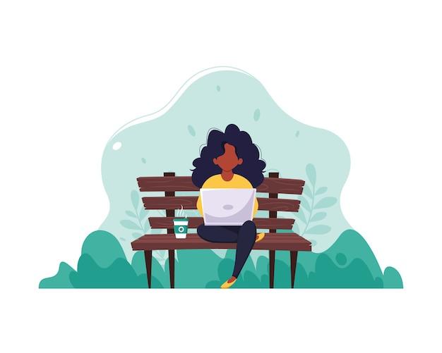 Schwarze frau, die auf einer bank mit einem laptop und kaffee sitzt. das konzept von fernarbeit, freiberuflicher tätigkeit und e-learning. in einem flachen stil.