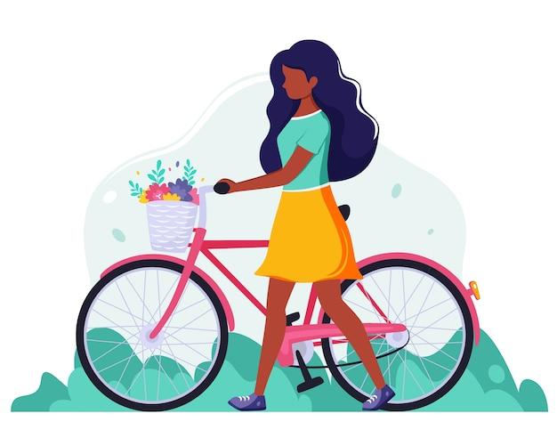 Schwarze frau mit einem fahrrad mit blumen im korb. außenaktivität. illustration im flachen stil.