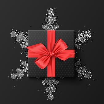 Schwarze geschenkbox. auf einer silbernen schneeflocke. auf einem dunklen hintergrund. illustration